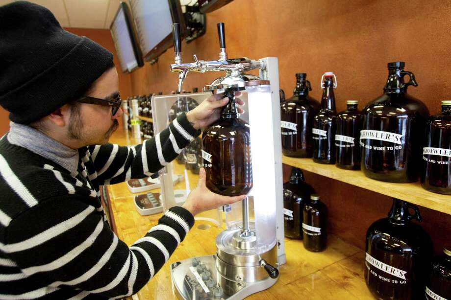 Jeremy Samaniego prepares a growler to be filled with beer at Growlers Beer & Wine To Go Tuesday, Jan. 29, 2013, in Houston. ( Brett Coomer / Houston Chronicle ) Photo: Brett Coomer, Houston Chronicle / © 2013 Houston Chronicle