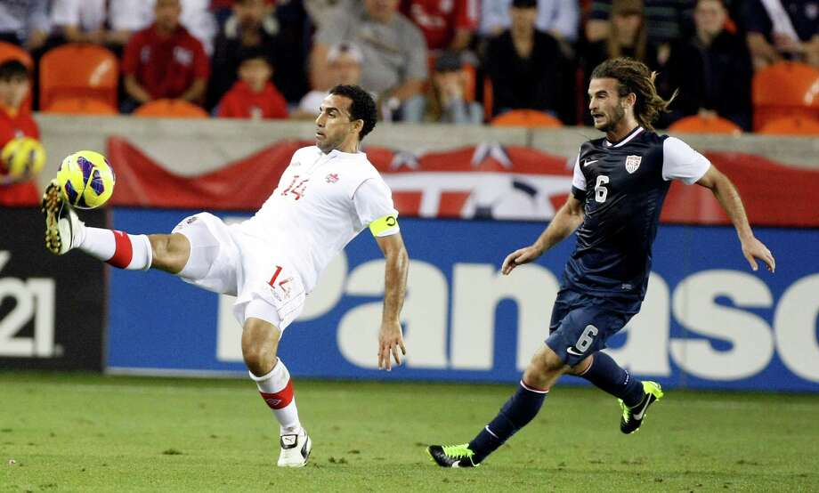 Canada's Dwayne De Rosario attempts a backwards pass as USA's Kyle Beckerman tries to defend during the second half. Photo: Nick De La Torre, Houston Chronicle / © 2013  Houston Chronicle