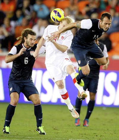 USA's Kyle Beckerman, left, and Brad Davis, right, work to keep the ball away from Canada's Kyle Bekker during the second half. Photo: Nick De La Torre, Houston Chronicle / © 2013  Houston Chronicle