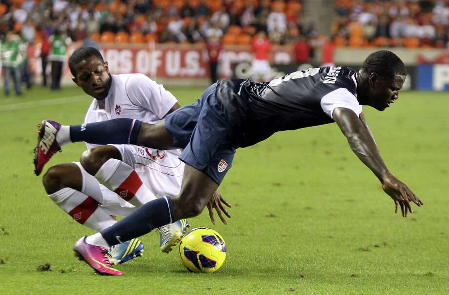 USA's Eddie Johnson, front, is tackled by Canada's Doniel Henry during the second half. Photo: Nick De La Torre, Houston Chronicle / © 2013  Houston Chronicle
