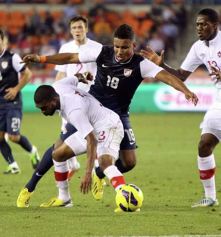 Canada's Ashtone Morgan, front, is called for a foul as he tries to stop USA's Juan Agudelo during the second half. Photo: Nick De La Torre, Houston Chronicle / © 2013  Houston Chronicle