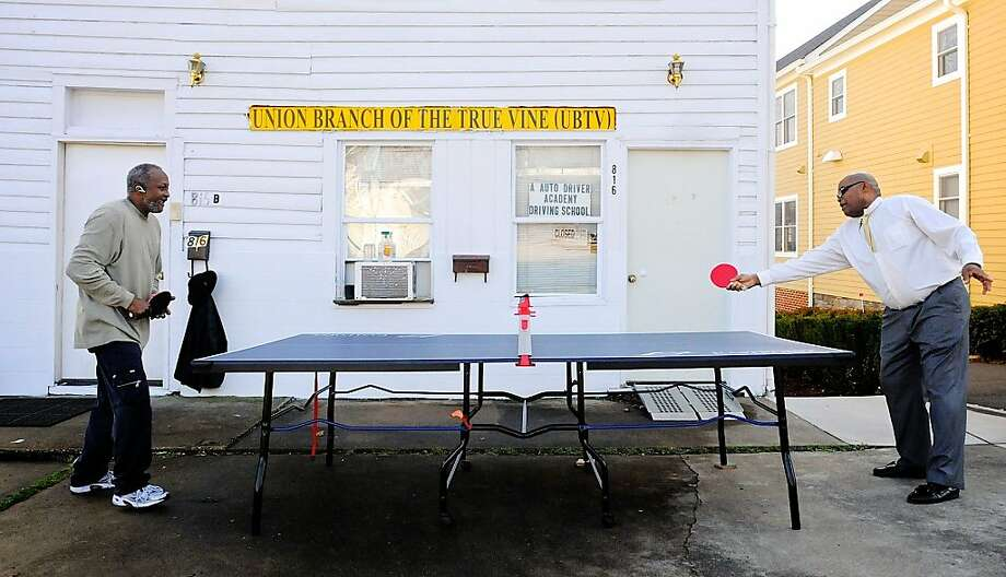 A.J. Horne, left, and Quintin C. Hardy play a game of table tennis in front of Horne's home in Fredericksburg, Va., during an unseasonably warm Tuesday, Jan. 29, 2013.  Photo: Robert A. Martin, Associated Press