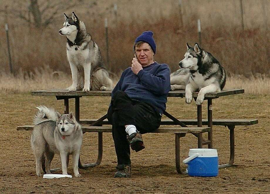 The sled-dog race is canceled? You don't say:Mike Burke takes a cell phone call while resting with his huskies during a walk in unseasonably warm weather in Wauconda, Ill. Photo: Bob Chwedyk, Associated Press