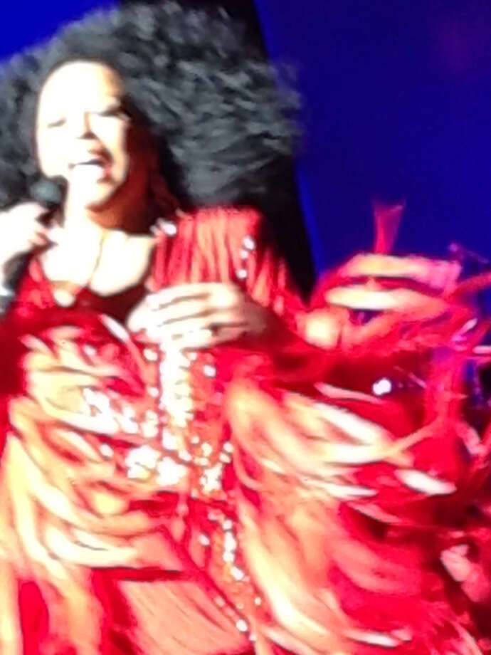 Diana Ross works the stage at the Majestic Theatre belting out a song amid sequins and feathers and all that hair. She often had to brush her hair away from her face with a hand.