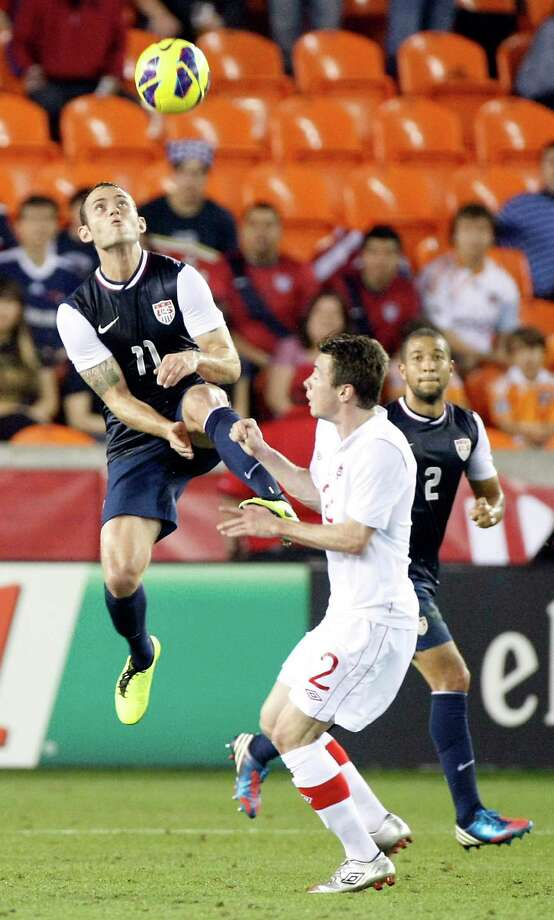 Brad Davis, left, soars to meet the ball head-on and prevent Canada's Nik Ledgerwood from getting in on the action during a friendly at BBVA Compass Stadium. Photo: Nick De La Torre, Staff / © 2013  Houston Chronicle