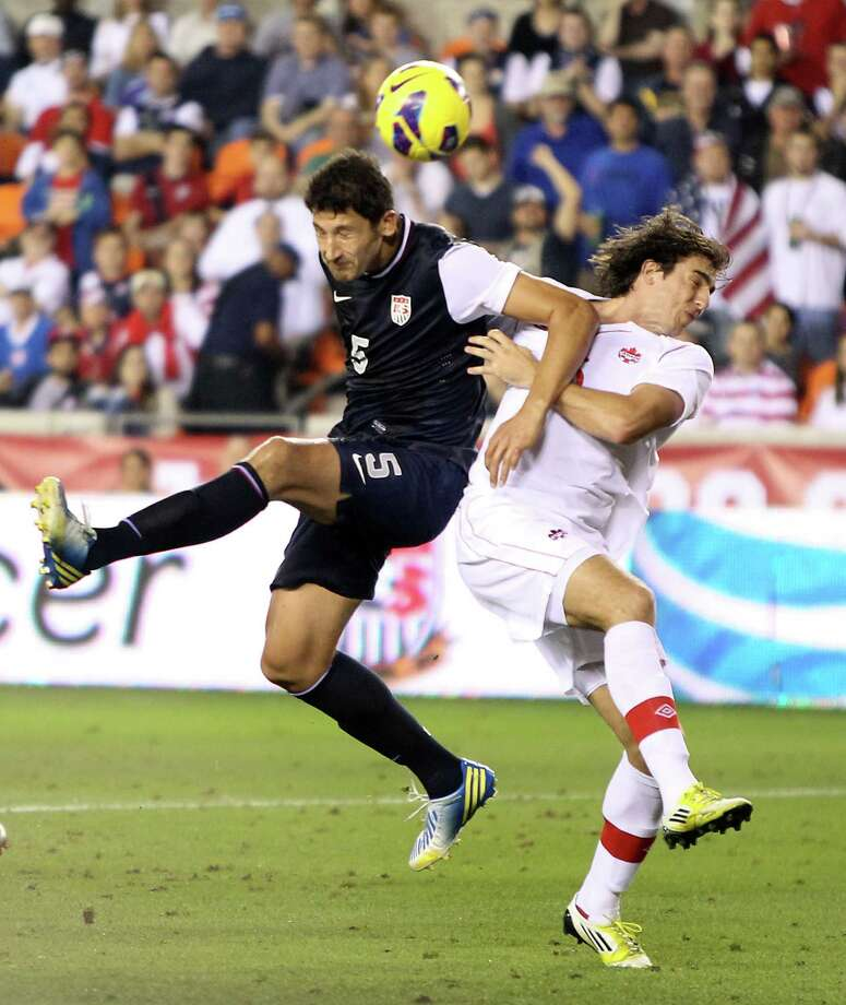 Omar Gonzalez, left, has his shot on goal broken up by Canada's Matthew Stinson during the second half Tuesday night at BBVA Compass Stadium. Photo: Nick De La Torre, Staff / © 2013  Houston Chronicle