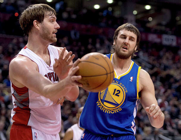 Golden State Warriors center Andrew Bogut, right, guards Toronto Raptors center Aaron Gray, left, as he passes off the ball during first half NBA action in Toronto on Monday, Jan. 28, 2013. Photo: Frank Gunn, Associated Press / CP