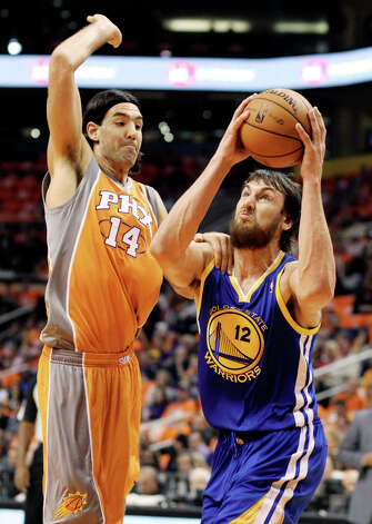 Golden State Warriors center Andrew Bogut, right, of Australia, drives to the basket past Phoenix Suns forward Luis Scola, left, of Argentina, in the first quarter of an NBA basketball game, Wednesday, Oct. 31, 2012, in Phoenix. Photo: Paul Connors, Associated Press / FR5880 AP