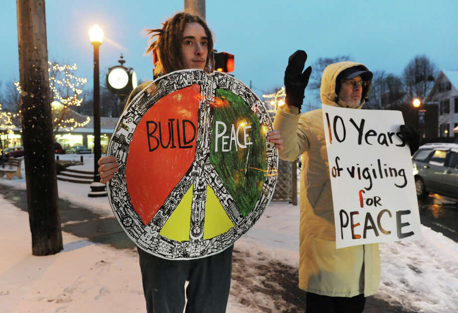 Maxmilian Karcker, left, of Albany and David Easter of Delmar hold signs for peace on the corner of Delaware and Kenwood Avenues as on Monday Jan. 28, 2013 in Delmar, N.Y.  Bethlehem Neighbors participated in a vigil that commemorates over 500 peace vigils held at the Four Corner since 2003. (Lori Van Buren / Times Union) Photo: Lori Van Buren