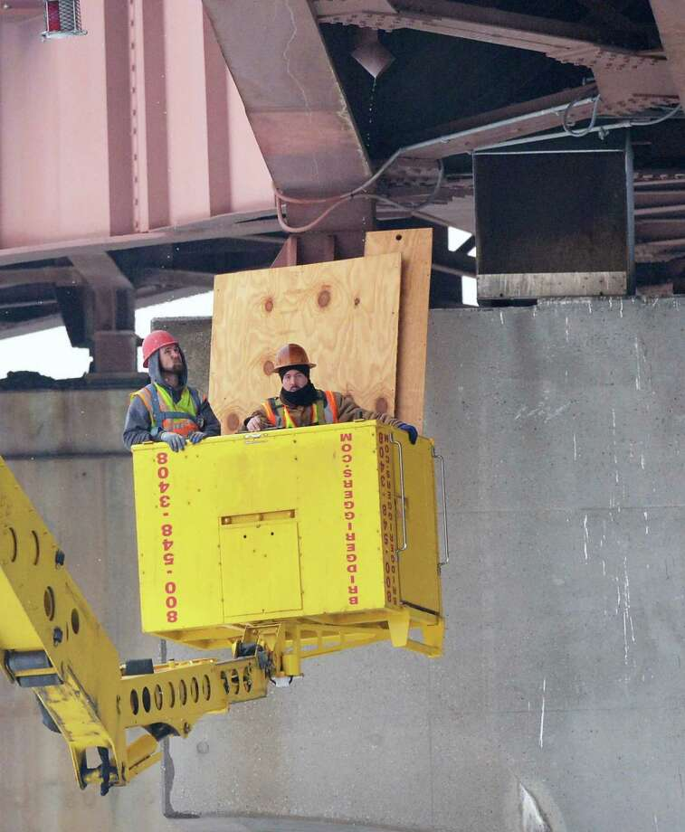 Workers remove covers from peregrine falcon nesting boxes on Dunn Memorial Bridge Tuesday Jan. 29, 2013, in Albany, N.Y. The screening was installed in February 2011 to protect the boxes  before the start of work on the bridge, DOT officials said. (John Carl D'Annibale / Times Union) Photo: John Carl D'Annibale / 00020935A