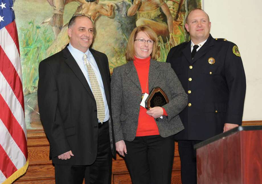 Investigator Laura Emanatian stands in between Lt. John Catone, Detective Division Commander of the Saratoga Springs Police Department and Lt. Sean Briscoe, right, after being announced the winner of the 2012 Officer of the Year award at Saratoga Springs City Hall on Tuesday Jan. 29, 2013 in Saratoga Springs, N.Y. (Lori Van Buren / Times Union) Photo: Lori Van Buren