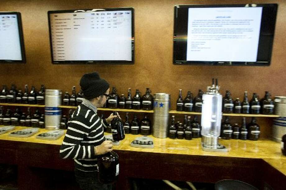 Samaniego works the bar with the beer lineup displayed on big screens above him.