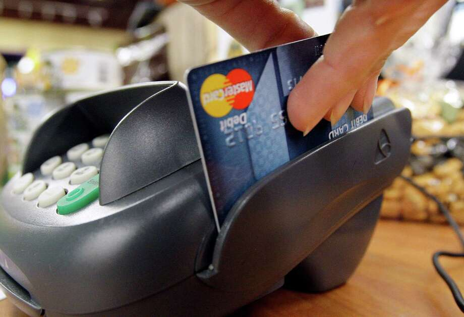 FILE - In this Nov. 2, 2009 file photo, a customer swipes a MasterCard debit card through a machine while checking-out at a shop in Seattle.  Consumers are wedged in the middle of a fight between bankers and merchants as the Senate plans a showdown vote Wednesday June 8, 2011 over whether to limit fees that stores pay financial institutions every time a debit card is swiped.    (AP Photo/Elaine Thompson, file) Photo: Elaine Thompson, Associated Press / AP2009