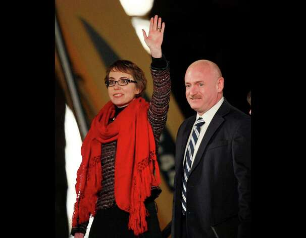 FILE - Rep. Gabrielle Giffords, left, and her husband, former astronaut Mark Kelly, wave at the start of a memorial vigil remembering the victims and survivors one year after the Arizona congresswoman was wounded in a shooting that killed six others, in this Jan. 8, 2012 file photo taken in Tucson, Ariz. Among those testifying Wednesday Jan. 30, 2013 at the year's first Senate hearing on what lawmakers should do to curb gun violence, will be Mark Kelly, husband of Giffords and a retired astronaut. Giffords, an Arizona Democrat, received a severe head wound in a 2011 shooting as she met with constituents outside a Tucson supermarket. Six people were killed and 12 others wounded. Photo: Matt York