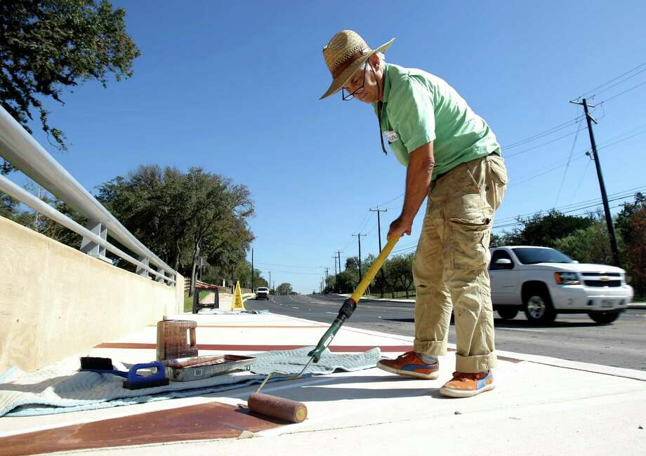 Artist Mark Schlesinger is currently working on a public art project for the city. He is painting sidewalks, a bridge, utility covers, guard rails, medians etc. along the 2.4 mile stretch between Thousand Oaks and Redland. When he is done Schlesinger says he will have created the world's largest painting. Photo: Helen L. Montoya, SAN ANTONIO EXPRESS-NEWS / SAN ANTONIO EXPRESS-NEWS