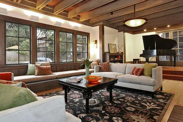 The grand living room of the two-story Craftsman home has a bay window with a window seat next to the performance stage. Photo: Liz Rusby