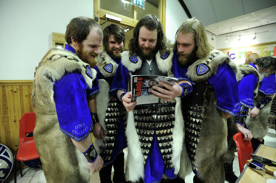 Participants dressed as Vikings look through a programme of events as they prepare to participate in