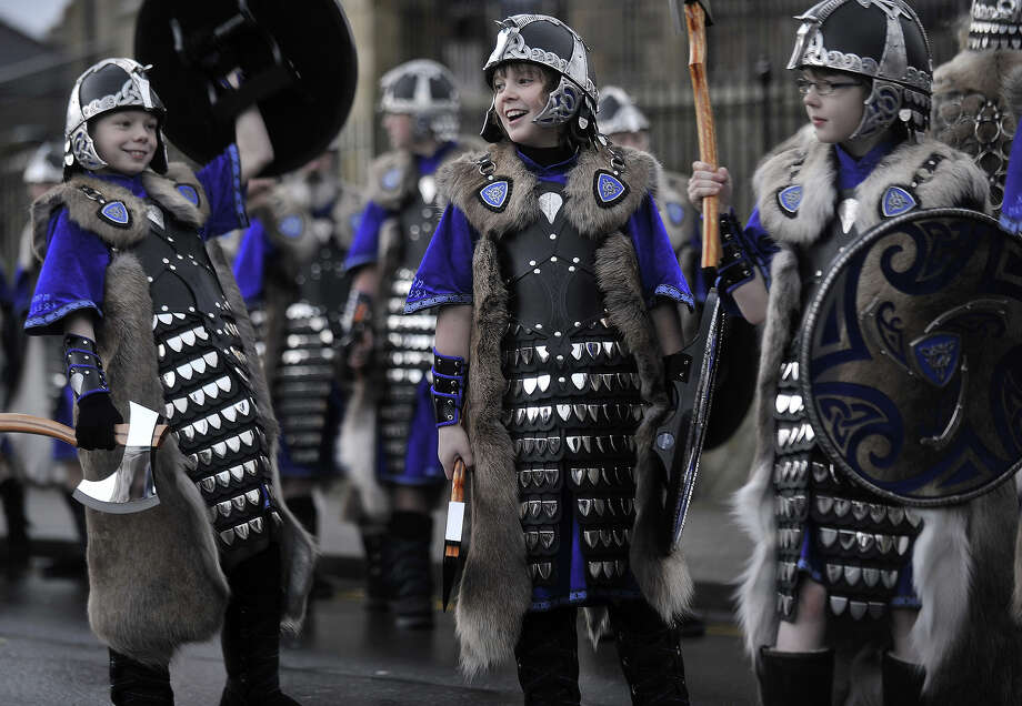 A young participant dressed as a Viking looks on as he prepares to participate in the annual Up Helly Aa festival in Lerwick, Shetland Islands on January 29, 2013. Up Helly Aa celebrates the influence of the Scandinavian Vikings in the Shetland Islands and culminates with up to 1,000 'guizers' (men in costume) throwing flaming torches into their Viking longboat and setting it alight later in the evening. Photo: AFP, AFP/Getty Images / 2013 AFP