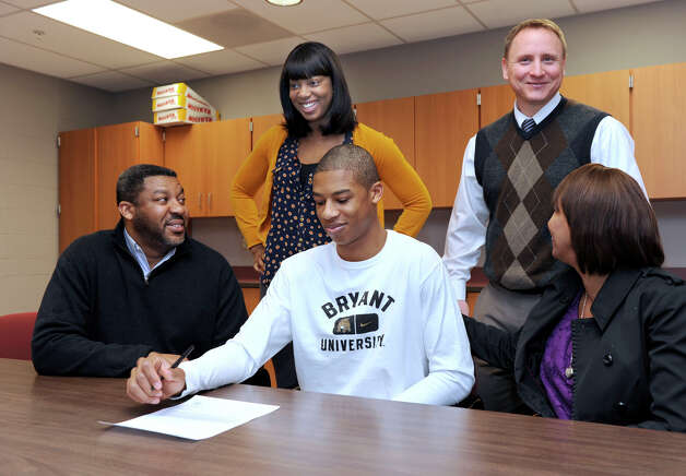 Daniel Garvin, 17, a Bethel High School basketball star, has signed a Letter of Intent to play Division I at Bryant University next year. There was a small ceremony for him at the high school Wednesday, January 30, 2013. With him were his parents Paul, left, and Rosemarie Garvin, his sister, Krystal, 24, and Ray Turek, the school's varsity head boys basketball coach. Photo: Carol Kaliff / The News-Times