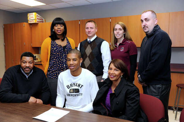 Daniel Garvin, 17, a Bethel High School basketball star, center, has signed a Letter of Intent to play at Division I  Bryant University next year. There was a small ceremony for him at the high school Wednesday, January 30, 2013. With him are his parents, Paul and Rosemarie Garvin, seated. Standing from left, his sister, Krystal Garvin, 24, Ray Turek, varsiety basketball head coach, Jayme McGovern, athletic director and Dennis Morsey, assistant coach. Photo: Carol Kaliff / The News-Times