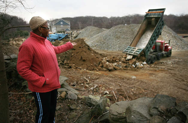 Rose Meekins of Bridgeport points out what she thinks is illegal dumping of large rocks on Mark IV Construction's property at 1234 Huntington Turnpike in Bridgeport on Wednesday, February 15, 2012. The property abuts the back yard of Meekin's 45 Iwanicki Circle home. On January 30, 2013, Superior Court Judge Richard Gilardi Wednesday refused a city request to block further construction on a three and a half-acre site on Huntington Turnpike where developer Manuel Moutinho plans to put up a 19,500 square foot shopping center. Photo: Brian A. Pounds / Connecticut Post