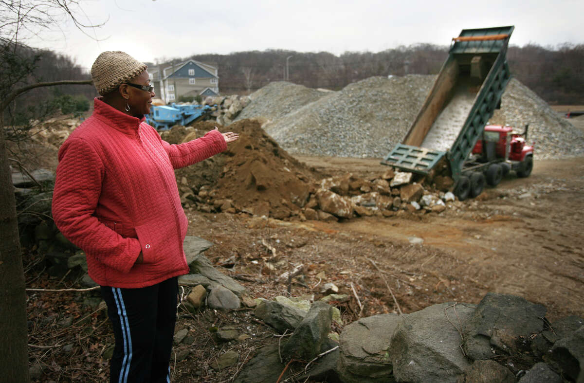 Rose Meekins of Bridgeport points out what she thinks is illegal dumping of large rocks on Mark IV Construction's property at 1234 Huntington Turnpike in Bridgeport on Wednesday, February 15, 2012. The property abuts the back yard of Meekin's 45 Iwanicki Circle home. On January 30, 2013, Superior Court Judge Richard Gilardi Wednesday refused a city request to block further construction on a three and a half-acre site on Huntington Turnpike where developer Manuel Moutinho plans to put up a 19,500 square foot shopping center.