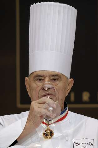 French chef Paul Bocuse drinks as he tastes a dish