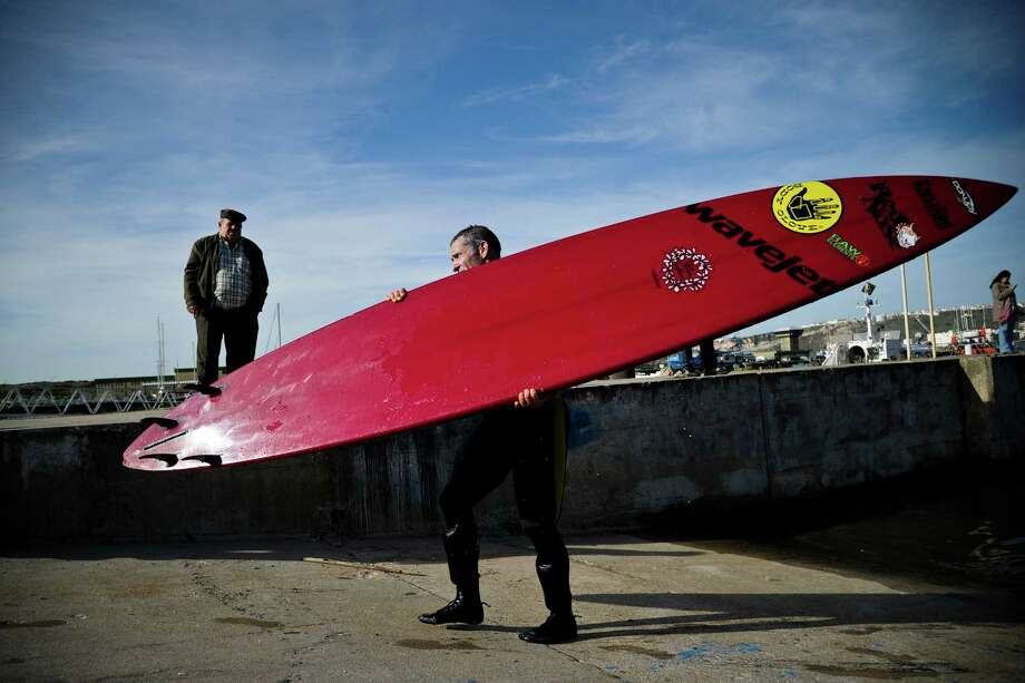 Hawaiian surfer Garrett McNamara carries his surfboard at Nazare's fishing harbor on Tuesday. (PATRICIA DE MELO MOREIRA/AFP/Getty Images) Photo: AFP, Ap/getty / 2013 AFP