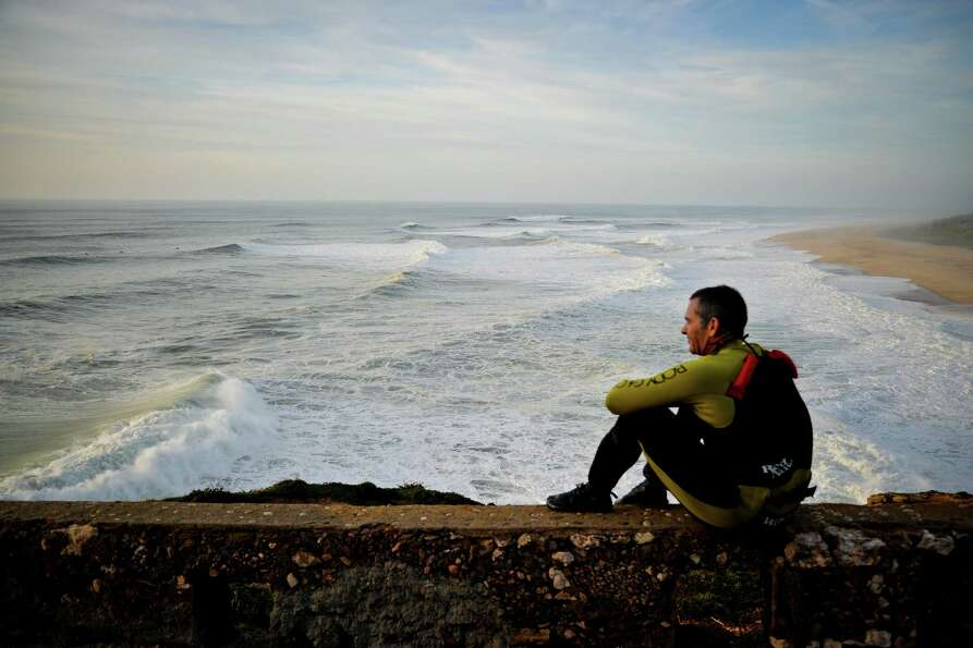 Hawaiian surfer Garrett McNamara looks at the ocean after taking part in a surf session at Praia do