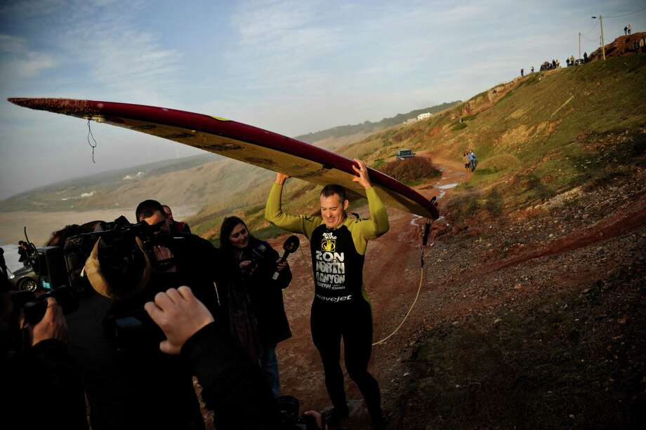 Hawaiian surfer Garrett McNamara carries his surfboard as he leaves the beach after a surf session at Praia do Norte in Nazare on Tuesday. (PATRICIA DE MELO MOREIRA/AFP/Getty Images) Photo: AFP, Ap/getty / 2013 AFP
