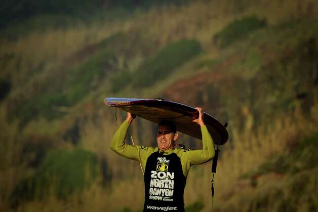 "Hawaiian surfer Garrett McNamara carries his surfboard as he leaves the beach after a surf session at Praia do Norte in Nazare on Tuesday. McNamara arrived onMonday at Praia do Norte, the ""north beach"" in the village of Nazare, central Portugal, in an attempt to break his own record for the largest wave ever surfed in the world. (PATRICIA DE MELO MOREIRA/AFP/Getty Images) Photo: AFP, Ap/getty / 2013 AFP"