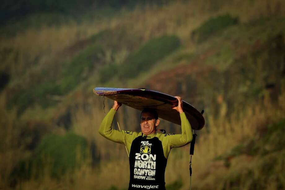 """Hawaiian surfer Garrett McNamara carries his surfboard as he leaves the beach after a surf session at Praia do Norte in Nazare on Tuesday. McNamara arrived onMonday at Praia do Norte, the """"north beach"""" in the village of Nazare, central Portugal, in an attempt to break his own record for the largest wave ever surfed in the world. (PATRICIA DE MELO MOREIRA/AFP/Getty Images) Photo: AFP, Ap/getty / 2013 AFP"""