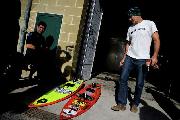 Hawaiian surfer Garrett McNamara fixes his surfboards before taking part in a surf session in Nazare on Tuesday. (PATRICIA DE MELO MOREIRA/AFP/Getty Images) Photo: AFP, Ap/getty / 2013 AFP