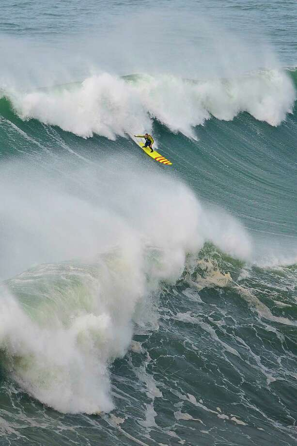 "US surfer Garrett McNamara rides a wave during a surf session at Praia do Norte in Nazare on Wednesday. McNamara holds the world record for the biggest wave surfed after riding a 78-foot (23.77 metre) breaker in Nazare, central Portugal, on Nov. 1, 2011, but on Monday was thought to have gone better at the same location. The 45-year-old from Hawaii was cautious about his exploit, though, telling reporters that he had ""no idea"" about the size of the wave and that his partner Kealii Mamala may even have set the new global benchmark.  (PATRICIA DE MELO MOREIRA/AFP/Getty Images) Photo: PATRICIA DE MELO MOREIRA, Ap/getty / 2013 AFP"