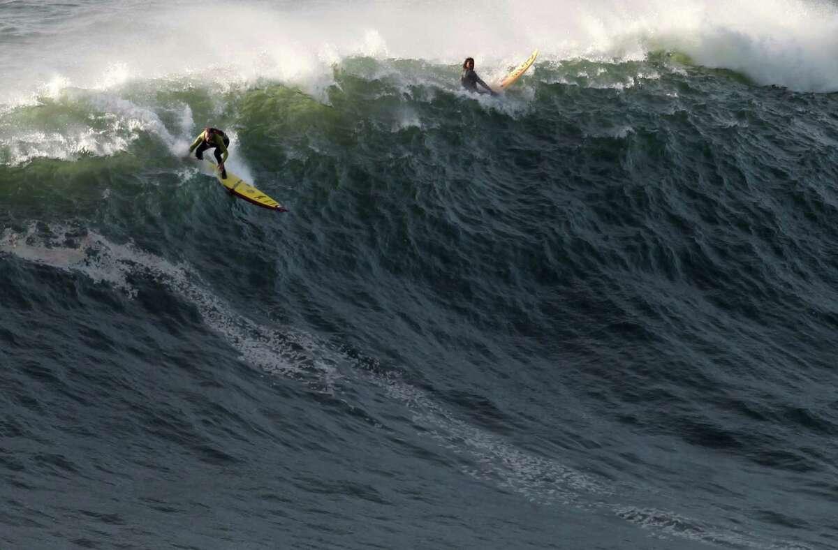 Garrett McNamara, left, makes a take off on a wave at Praia do Norte beach in Nazare, Portugal, on Tuesday. . (AP Photo/Francisco Seco)