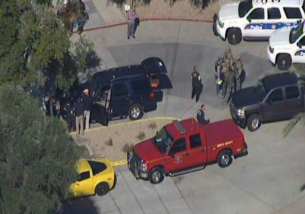 This frame grab provided by abc15.com shows the scene at a Phoenix office complex where police say someone shot at least three people on Wednesday, Jan. 30, 2013. Officer James Holmes said the victims were taken to hospitals and did not know if their injuries were life threatening. (AP Photo/abc15.com) MANDATORY CREDIT Photo: Associated Press / Abc15.com
