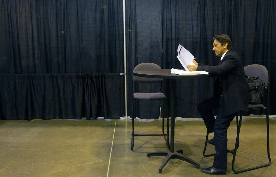 Al Alam reads over the itinerary during the Chron Mega Job Fair at Reliant Center, Wednesday, Jan. 30, 2013, in Houston. Photo: Cody Duty, Houston Chronicle / © 2013 Houston Chronicle