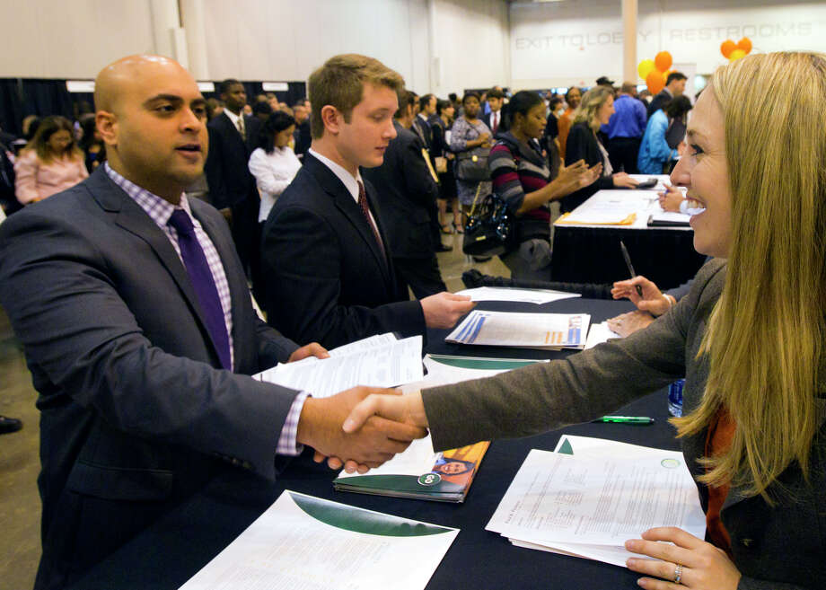 Omar Qureishi, left, shakes hands with Enterprise employee Meghan Bingham, right, during the Chron Mega Job Fair at Reliant Center, Wednesday, Jan. 30, 2013, in Houston. Photo: Cody Duty, Houston Chronicle / © 2013 Houston Chronicle