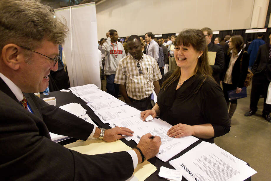 Vic Collins, left, speaks with Jennifer McDermott, right, during the Chron Mega Job Fair at Reliant Center, Wednesday, Jan. 30, 2013, in Houston. Photo: Cody Duty, Houston Chronicle / © 2013 Houston Chronicle