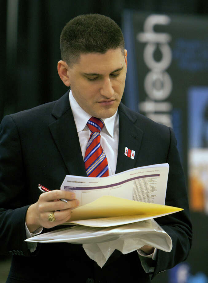 Eric Dekelbaum looks at an itinerary during the Chron Mega Job Fair at Reliant Center, Wednesday, Jan. 30, 2013, in Houston. Photo: Cody Duty, Houston Chronicle / © 2013 Houston Chronicle