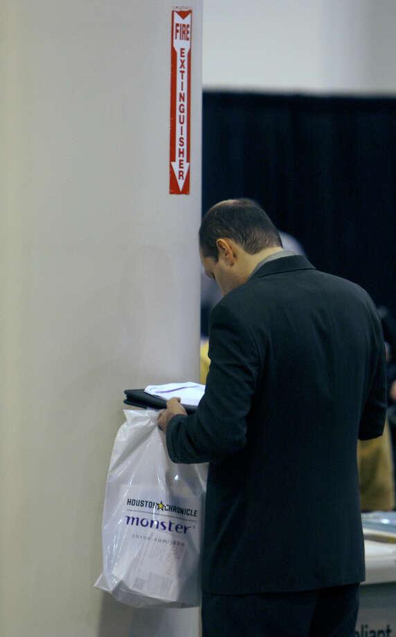 An applicant looks at paperwork at the Chron Mega Job Fair at Reliant Center, Wednesday, Jan. 30, 2013, in Houston. Photo: Cody Duty, Houston Chronicle / © 2013 Houston Chronicle