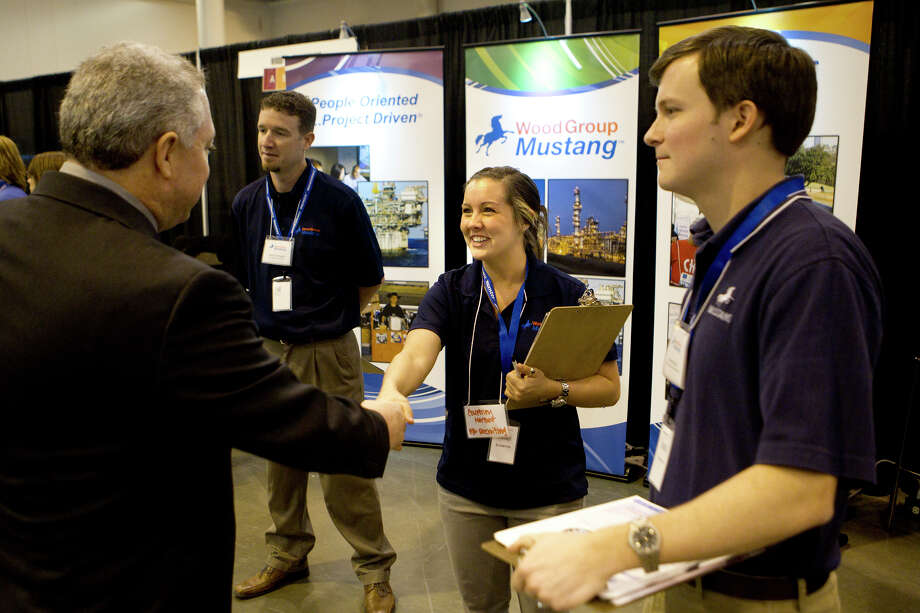 David Hooff shakes hands with Courtney Herzer as Chad Cunningham and Andrew Schuh look on during the Chron Mega Job Fair at Reliant Center, Wednesday, Jan. 30, 2013, in Houston. Photo: Cody Duty, Houston Chronicle / © 2013 Houston Chronicle