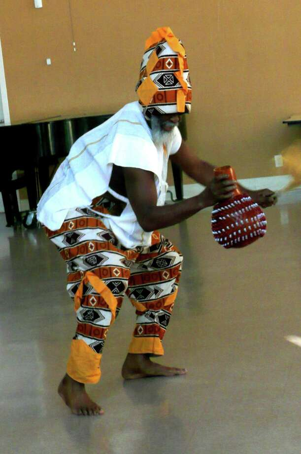 Baba Abishai, co-founder of the troupe, Sounds of Africa, plays the Djembe drum dressed in traditional African clothing during a recent performance for children of the Christ Church Greenwci nursery school. Photo: Anne W. Semmes