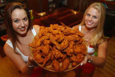 Hooters girls Shannon Kischefsky(left) and Casey Gandy hold a plate of Buffalo Wings that won the Readers Choice Award Friday May 17, 2002 at the restaurant on the Riverwalk. PHOTO BY EDWARD A. ORNELAS/STAFF