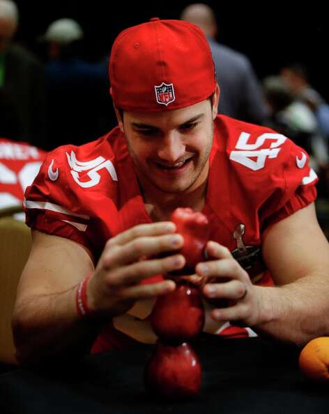 San Francisco 49ers practice squad linebacker Nate Stupar tries to balance apples while other player