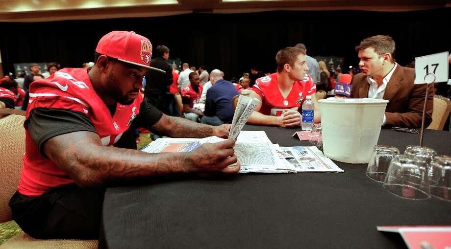 San Francisco 49ers tight end Delanie Walker, left, reads a newspaper between interviews during a media availability on Wednesday, Jan. 30, 2013, in New Orleans. The 49ers are scheduled to play the Baltimore Ravens in the NFL Super Bowl XLVII football game on Feb. 3. Photo: Mark Humphrey, Associated Press / AP