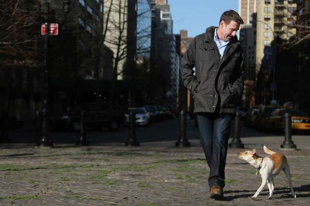 "In this Saturday, Jan. 19, 2013 photo, Michael Wright and his dog Toby (formerly called Fumble) pose for a portrait in New York.  ""Puppy Bowl,"" an annual two-hour TV special that mimics a football game with canine players, made its debut eight years ago on The Animal Planet. ""It raises awareness for our shelter and others that take part,"" said Madeline Bernstein, president and CEO of the Society for the Prevention of Cruelty to Animals Los Angeles.  ""A lot of people have come in during the last year and said, 'I want a dog just like Fumble,'"" she said, referring to spcaLA's entry in ""Puppy Bowl VIII"" who earned the game's Most Valuable Pup crown. (AP Photo/Mary Altaffer) Photo: Mary Altaffer"