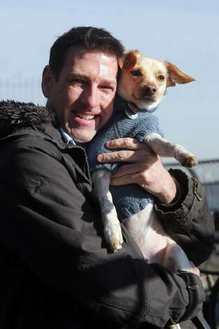 "In this Saturday, Jan. 19, 2013 photo, Michael Wright and his dog Toby pose for a portrait in New York.  Toby, previously named Fumble, last year's Animal Planets' ""Puppy Bowl"" MVP winner, was adopted before the show aired. Wright said he found out about Fumble's participation toward the end of the adoption process, and plans to watch this year's show to catch any flashbacks of last year's MVP playing his heart out. (AP Photo/Mary Altaffer) Photo: Mary Altaffer"