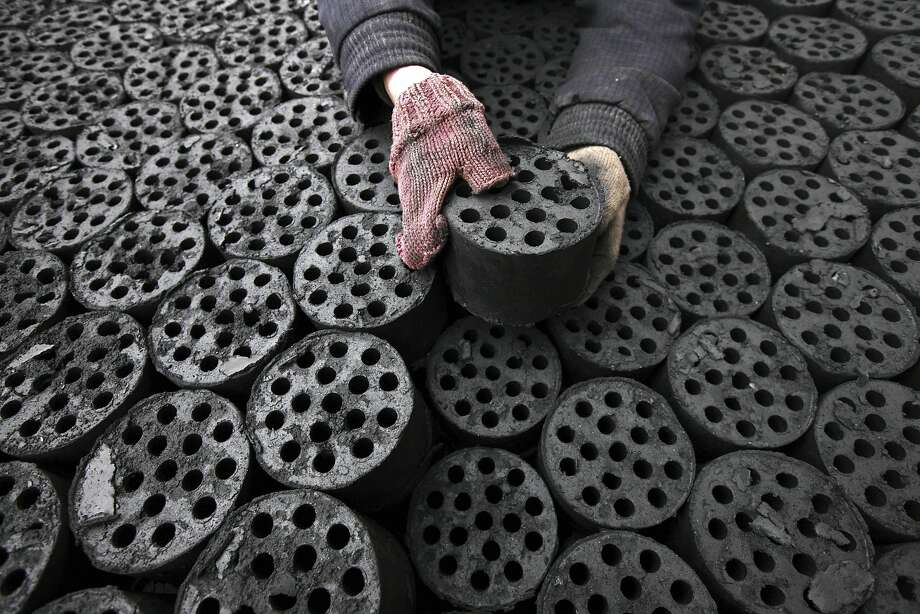 Pollution pucks: A worker stacks coal briquettes at a coal distribution business in Huaibei, China. The air quality index at Beijing Municipal Environmental Monitoring Centre reached 993 during the worst stretch of China's recent smog cloud - almost 40 times the World Health Organization's recommended safe limit. Photo: Str, AFP/Getty Images