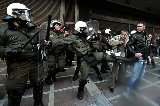 Protesters clash with riot police outside the Labour Ministry in Athens on January 30, 2013. Police were called in on Wednesday to dislodge around 30 Communist unionists from the labour ministry in a protest against new pension cut plans. The unionists were arrested and police used tear gas outside the building to disperse a larger group of protesters demanding their release. Photo: Aris Messinis, AFP/Getty Images